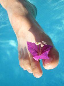 Noha s kvetom medzi prstami